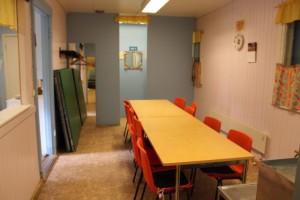 Röyläntuvan kerhohuone, jonne yleensä katetaan noutopöytä. Keittiö vasemmalla.